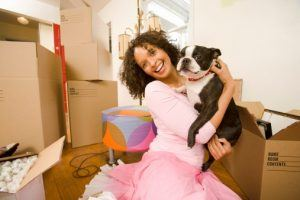 Woman holding dog in new home