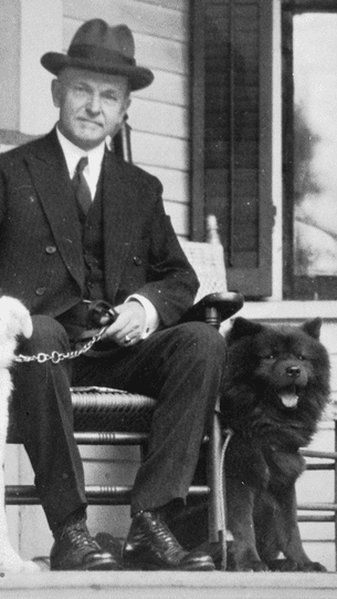 Calvin Coolidge alongside Tiny Tim, one of two Chows that resided at the White House during his term.
