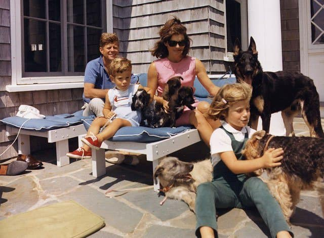 The Kennedy family poses with their dogs at Hyannisport: cocker spaniel Shannon, Welsh terrier Charlie, German shepherd Clipper, and the pups of Pushinka, who was a gift to Caroline from Soviet premier Nikita Khrushchev.